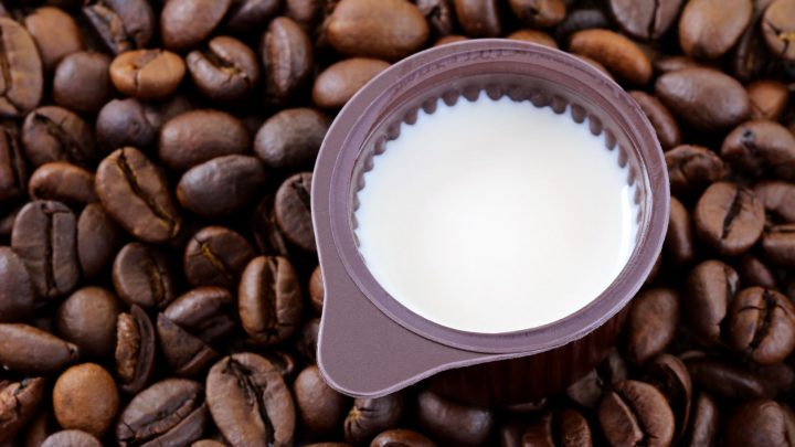 36854062 - a small cup of coffee creamer on coffee beans