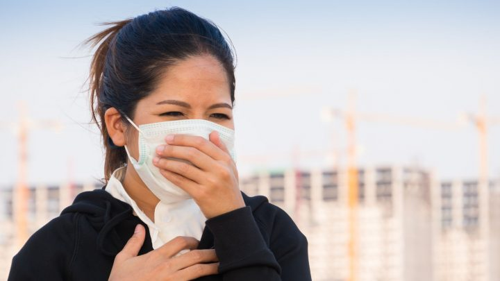 63643492 - asian woman wearing face mask and coughing by pollution