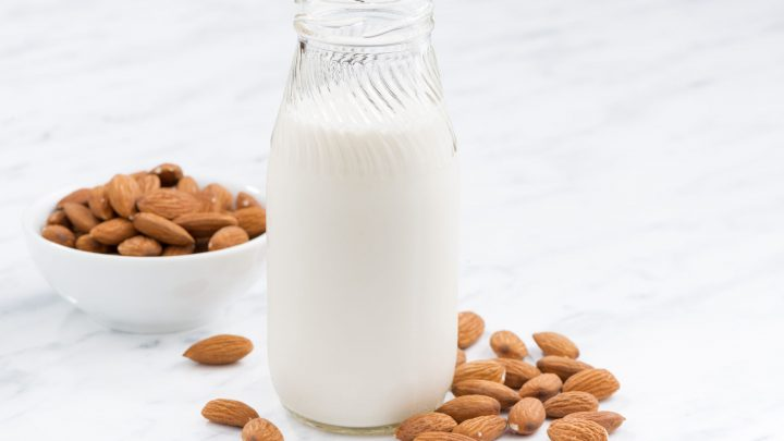 46168546 - almond milk in a glass bottle on white table, closeup, horizontal