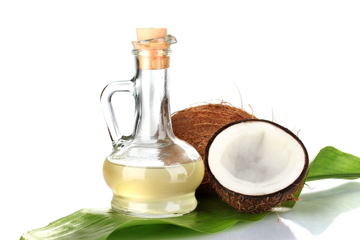 15455977 - decanter with coconut oil and coconuts isolated on white